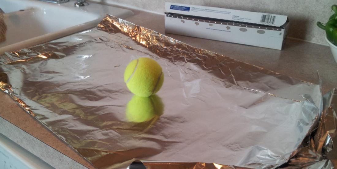 Elle enveloppe une balle de tennis avec du papier d'aluminium et la met dans la sécheuse