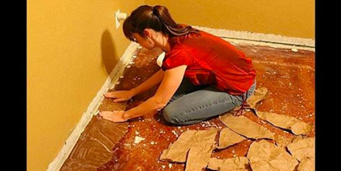 Elle recouvre son plancher de papier brun et elle obtient un plancher à l'aspect bois à une fraction du prix