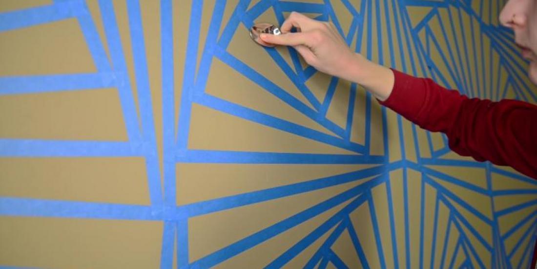 À l'aide d'une cuillère, elle applique du ruban adhésif sur les murs de sa chambre et la transforme complètement