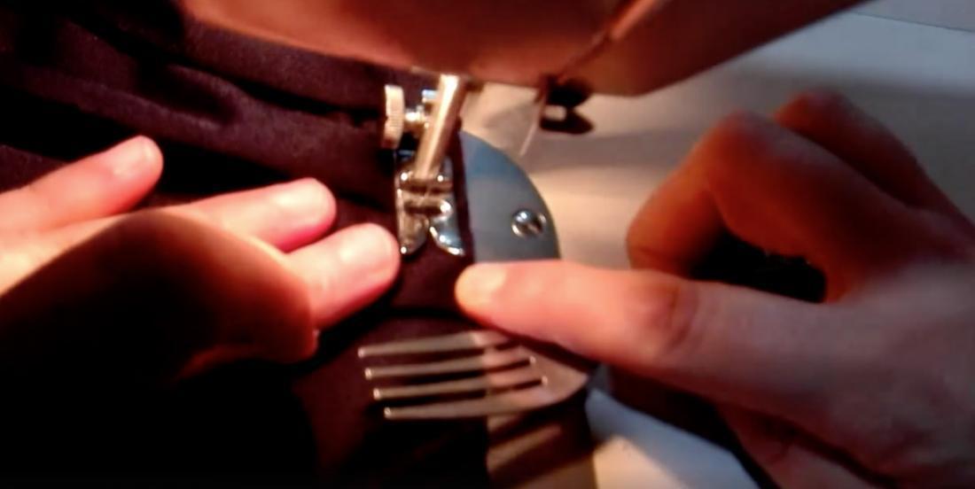 Elle utilise une fourchette pour tenir le tissu à coudre. Regardez bien comment elle procède.