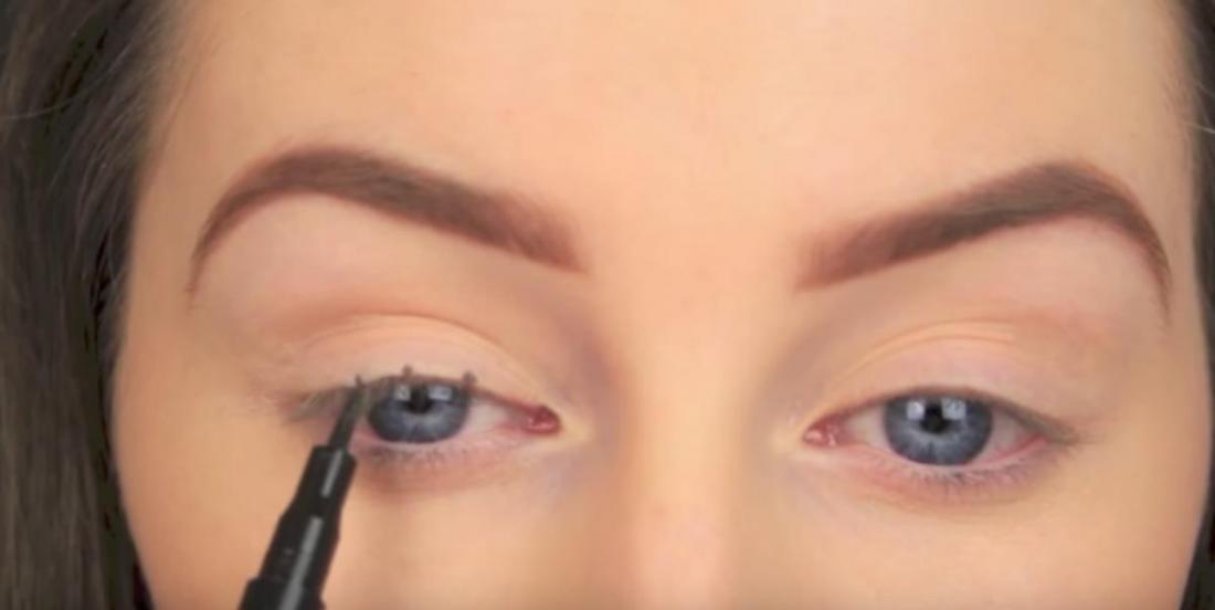 Elle trace de minuscules points sur sa paupière afin de créer un maquillage parfait.